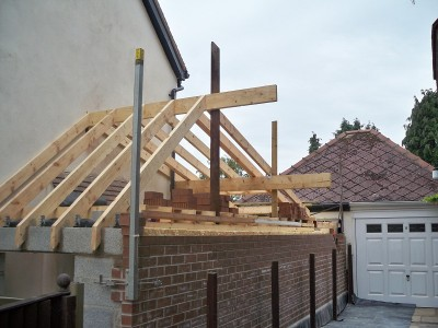 Installation of new roof trusses to form front porch and new extension roof. The roof extends to existing garage with a fibreglass flat roof in between.
