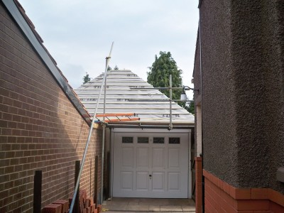 New roof on garage. View from neighbours drive. Existing asbestos tiles were safely removed under licence and disposed off as per current guidelines. Roof has been felted and battened ready for tiles.